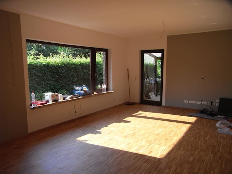 Das Wohnzimmer erhielt sandfarbene Wände und ebenso den Industrielamellenholzboden.: moderne Wohnzimmer von Grandi+Lutze