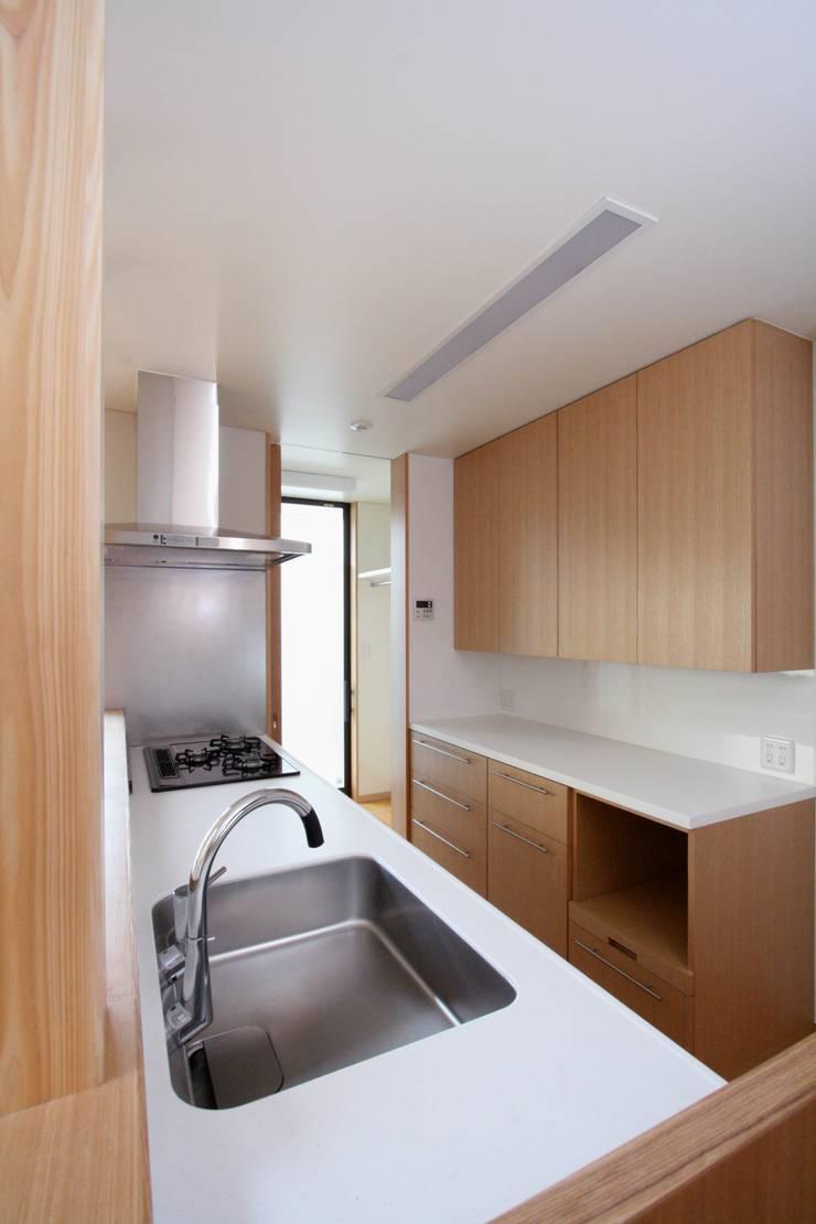 洗濯室兼サンルームとつながるキッチン: 中川龍吾建築設計事務所が手掛けたキッチンです。,モダン 木 木目調