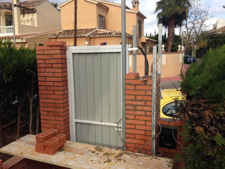 PUERTAS CON PILARES DE LADRILLO VISTO Y TEJADILLO:  de estilo  de Rudeco Construcciones