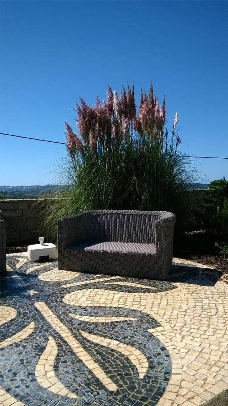 Terraço em calçada no centro de jardim de moradia privada: Jardins  por Roc2c