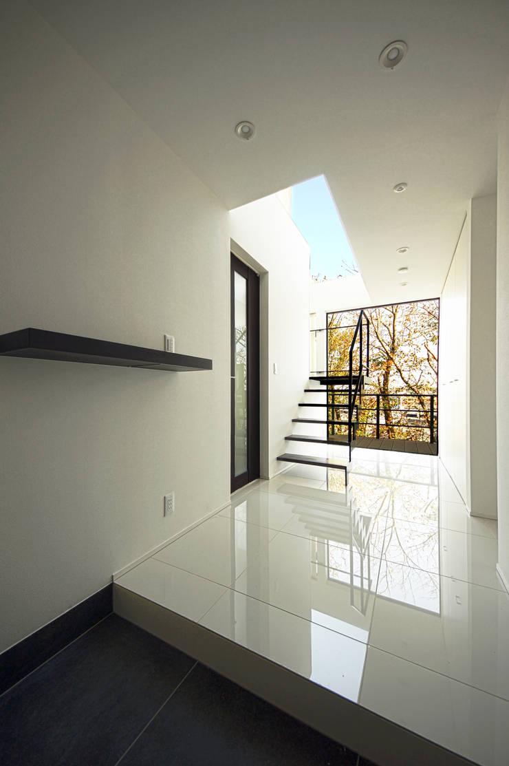 サクラと空が出迎える玄関: TERAJIMA ARCHITECTSが手掛けた廊下 & 玄関です。,