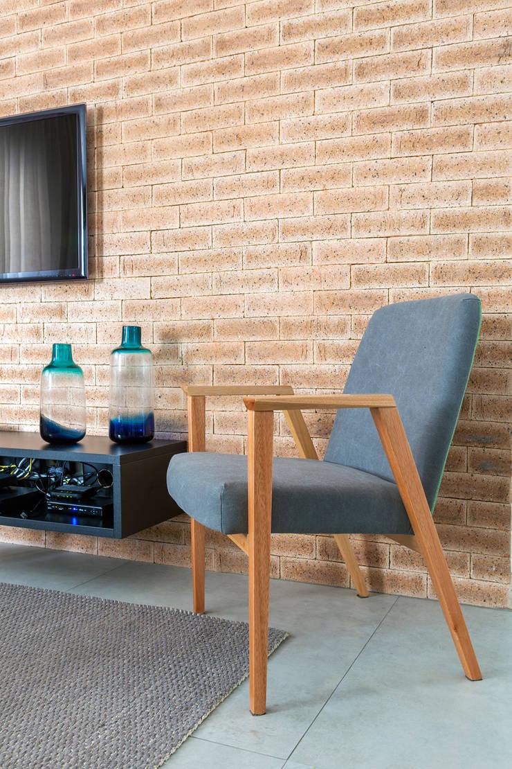 Detalhe da parede de tijolos: Sala de estar  por Márcio Campos Arquitetura + Interiores,