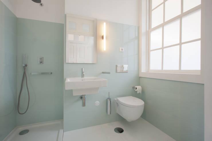 Porto Lounge Hostel: Casas de banho  por aaph, arquitectos lda.