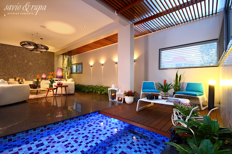 Mid Century Living Room with Water Body:  Living room by Savio and Rupa Interior Concepts