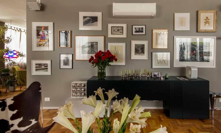 detalhe da parede com quadros: Salas de estar modernas por acr arquitetura