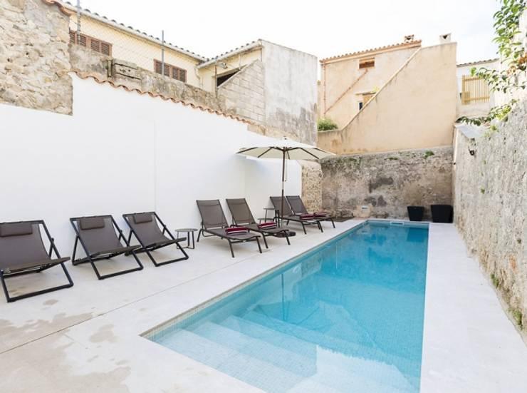 Diseño vintage para una casa de pueblo en Mallorca: Piscinas de estilo moderno de Bornelo Interior Design