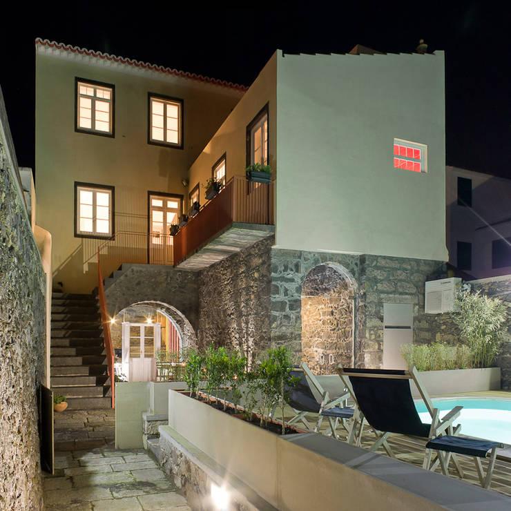 swimming pool deck by night: Piscinas rústicas por ARCO mais - arquitectura e construção
