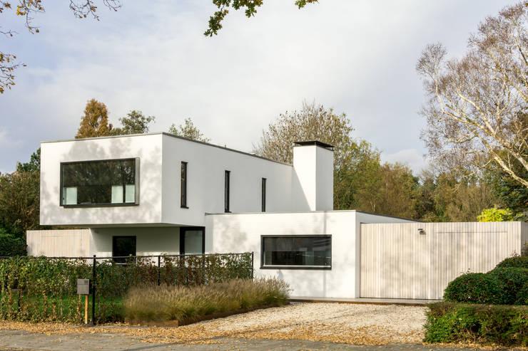 Luxe renovatie met zwevende dakopbouw, maatwerk keuken met zwevend HI-MACS keukenblok en houtfineer kastenwand: moderne Huizen door Joep van Os Architectenbureau