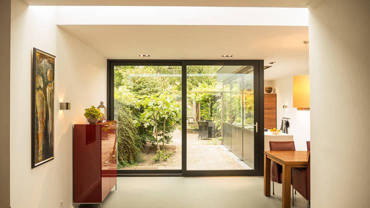 Luxe smalle aanbouw met keuken pal op het zuiden, aluminium schuifpui en lamellen zonwering:  Woonkamer door Joep van Os Architectenbureau, Modern