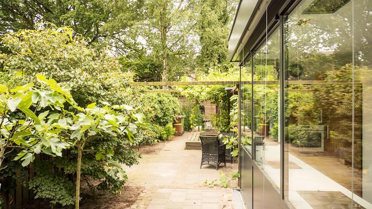 Luxe smalle aanbouw met keuken pal op het zuiden, aluminium schuifpui en lamellen zonwering:  Tuin door Joep van Os Architectenbureau, Modern