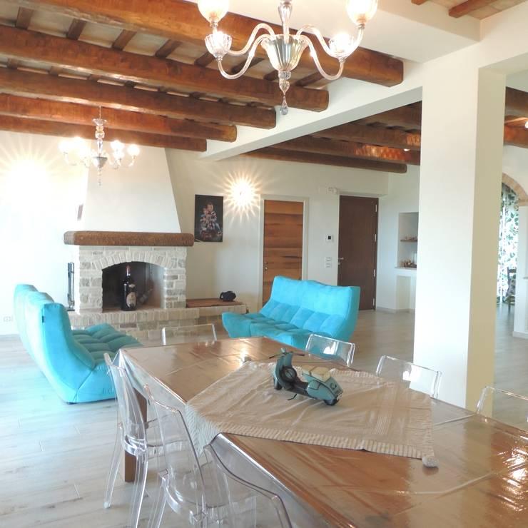 Ampio salotto con divani molto colorati e moderni in contrapposizione ad un ambiente rustico: Soggiorno in stile in stile Rustico di Nadia Moretti