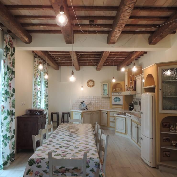Cucina rustica murata con piano piastrellato e ante in legno verniciato e invecchiato. Le lampade a sospensione danno più risalto alla travatura: Cucina in stile in stile Rustico di Nadia Moretti