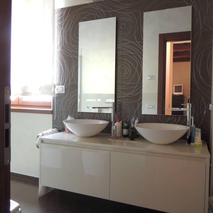 Mobile del bagno padronale con doppio lavabo a ciotola e doppio specchio; rivestimento in ceramica decorata: Bagno in stile in stile Moderno di Nadia Moretti