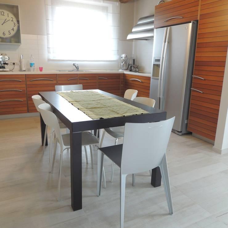 Cucina moderna in legno con frigo americano, cappa in acciaio e tavolo da pranzo: Cucina in stile  di Nadia Moretti
