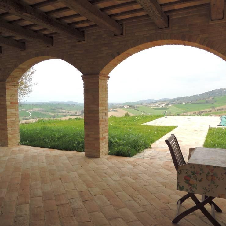 Veduta dell'esterno con camminamento verso la piscina in mattone rustico: Case in stile in stile Moderno di Nadia Moretti