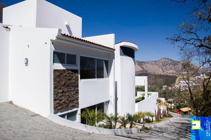 fachada lateral: Pasillos y recibidores de estilo  por Excelencia en Diseño