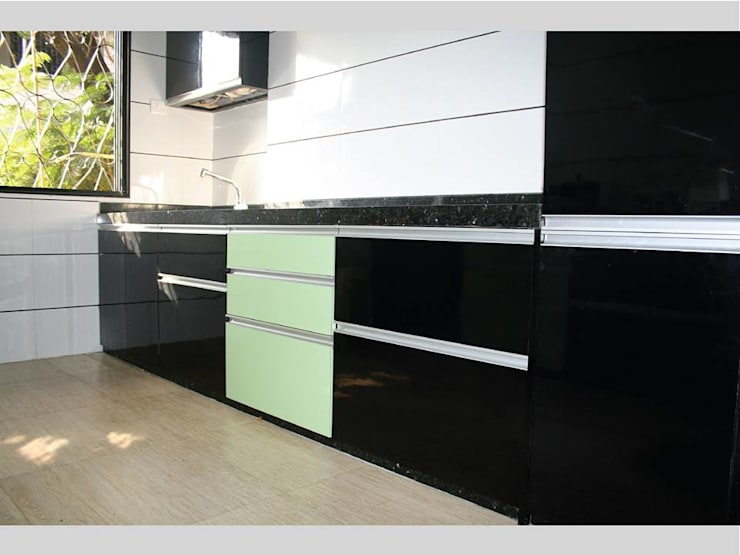 The integrated high-utility aluminum profile handles and black groutings enhance the space with the creation of endless horizontal lines: modern Kitchen by Neha Changwani