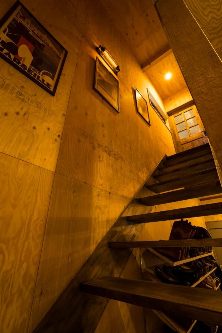大好きなバイクと暮らすラスティックな素材感を楽しむ住まい: QUALIAが手掛けた廊下 & 玄関です。