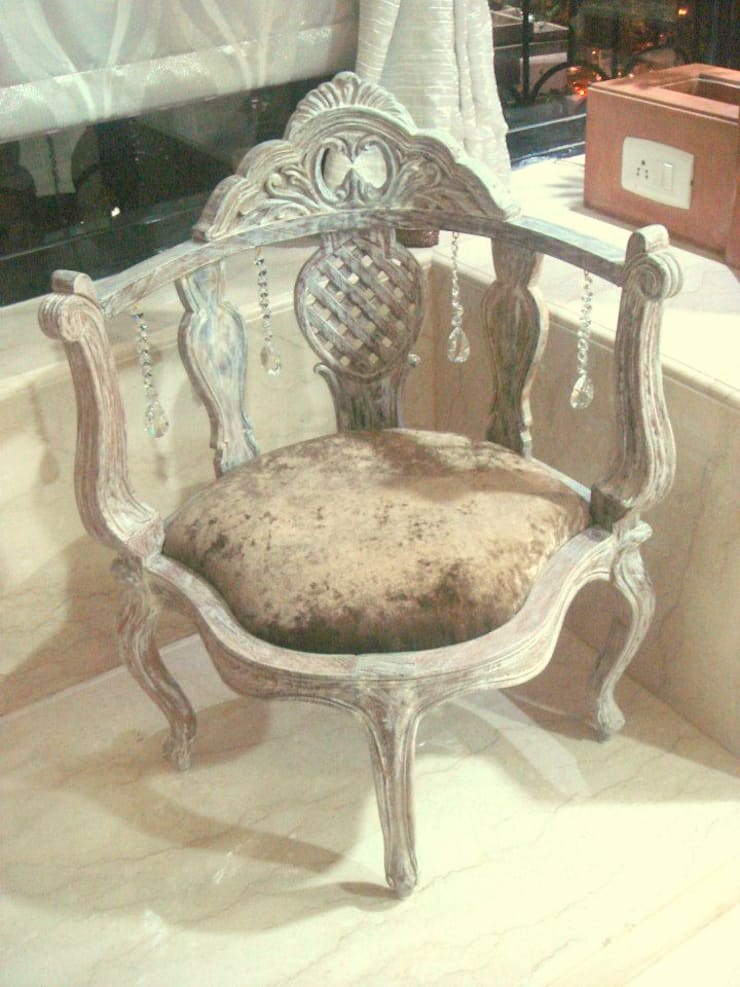 An arm chair in antique finish with customized crystal hangings.:  Living room by Neha Changwani