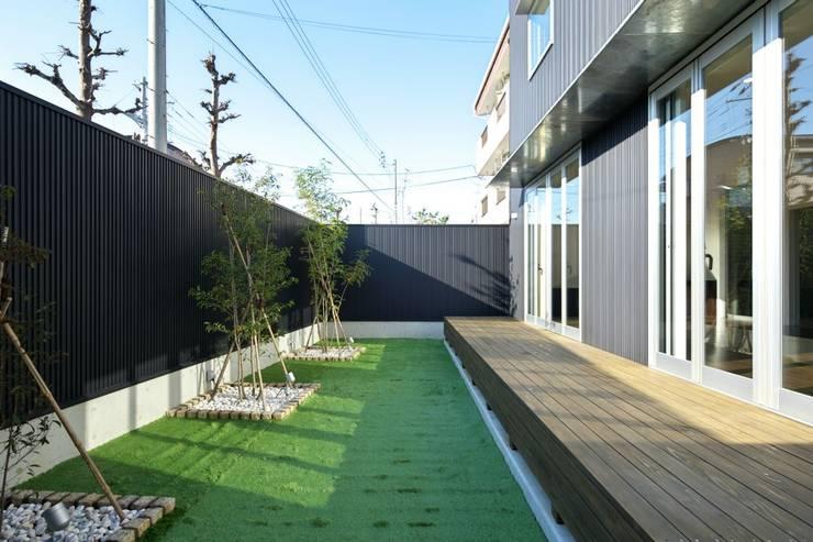 人工芝を用いたリビングとつながる庭: 有限会社 橋本設計室が手掛けた庭です。