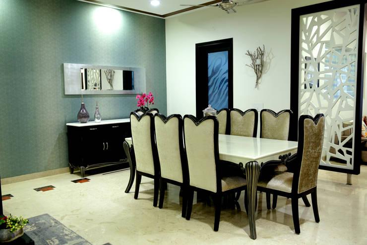 Dining area:  Dining room by renu soni interior design