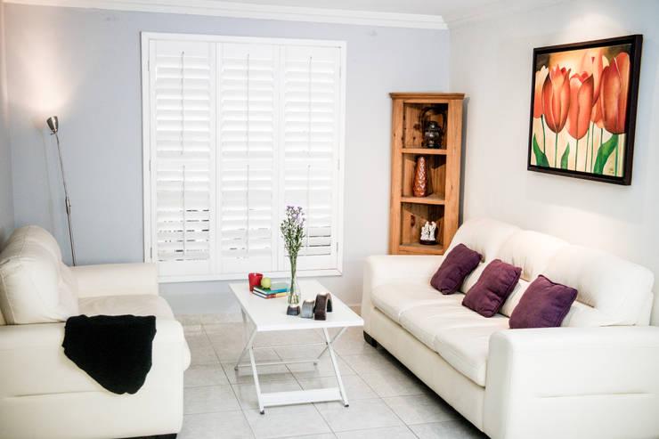 Shutter blanca de tres paneles en sala: Ventanas de estilo  por Whitewood Shutters