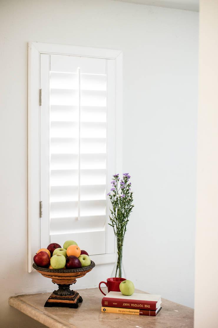Shutter blanca para ventana pequeña: Puertas y ventanas de estilo  por Whitewood Shutters