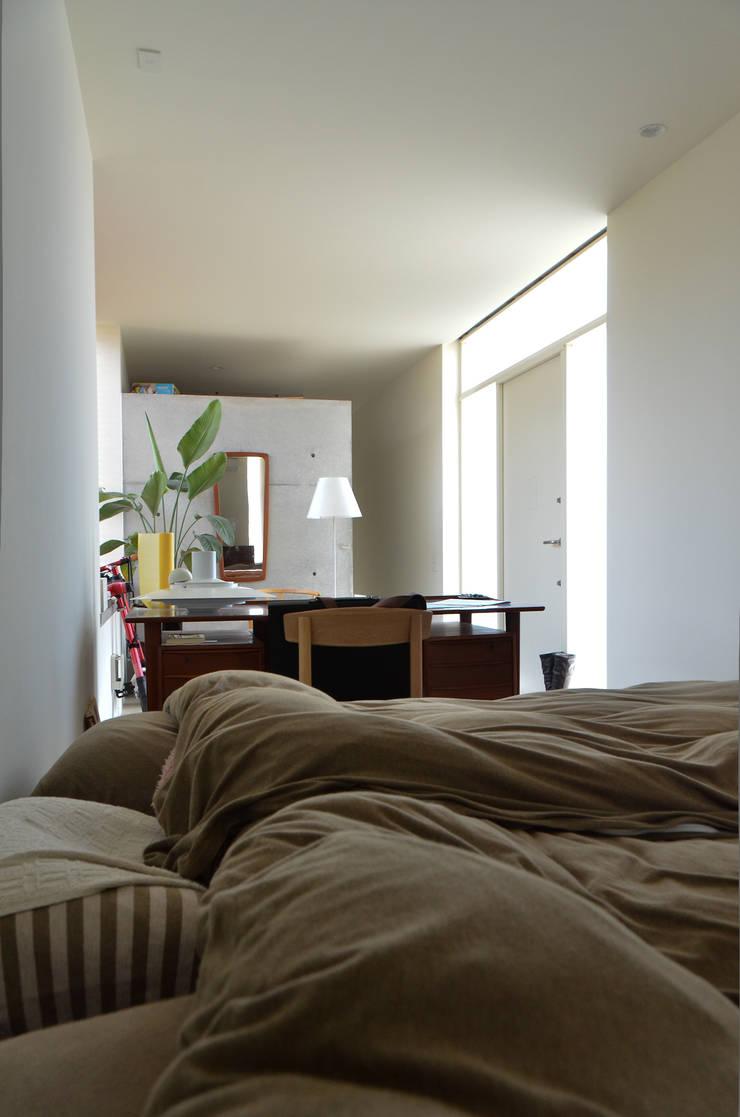 麦畑に囲まれた家: 風景のある家.LLCが手掛けた寝室です。