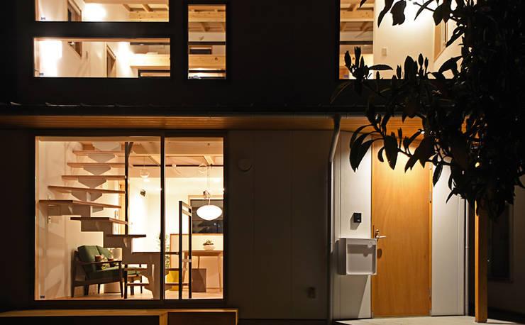 窓からこぼれる柔らかな灯が印象的な外観: 合同会社negla設計室が手掛けた家です。,