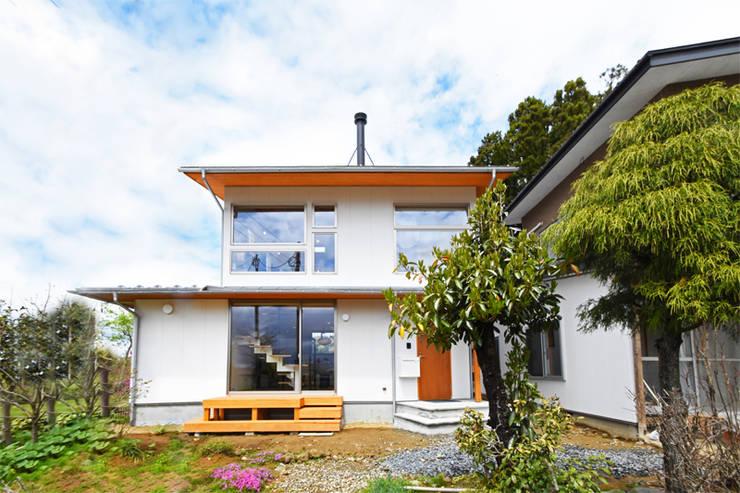 大窓と薪ストーブの煙突がアクセントの外観: 合同会社negla設計室が手掛けた家です。,
