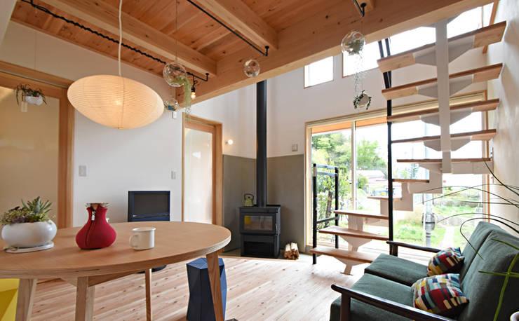 スタイリッシュな薪ストーブのある明るいリビング: 合同会社negla設計室が手掛けたリビングです。,