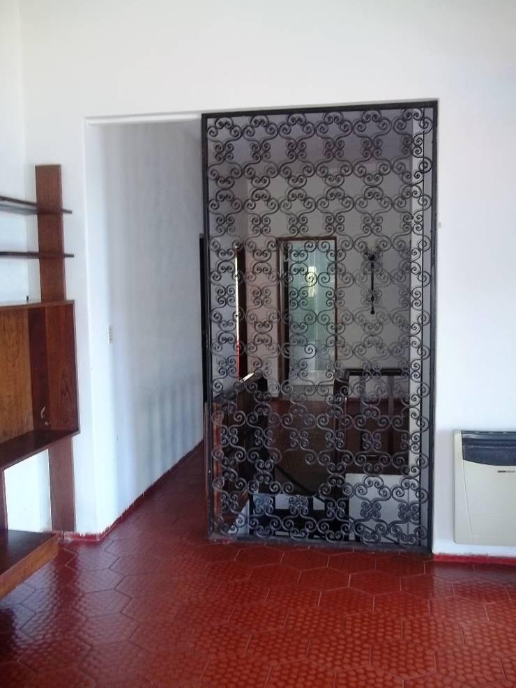 Pasillo de distribución: Pasillos y recibidores de estilo  por Liliana almada Propiedades