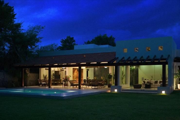 FACHADA TRASERA VISTA NOCHE: Jardines de estilo  por AIDA TRACONIS ARQUITECTOS EN MERIDA YUCATAN MEXICO