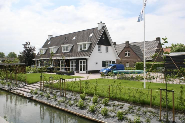 Landelijke woning met wit gevelstucwerk en zwart potdekselwerk.:  Huizen door Brand BBA I BBA Architecten, Landelijk Hout Hout