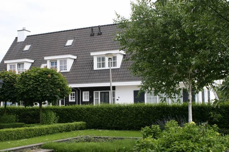 Landelijke woning met wit gevelstucwerk en zwart potdekselwerk.:  Huizen door Brand BBA I BBA Architecten, Landelijk