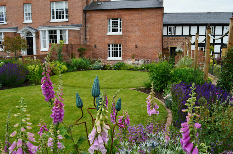 Circular lawns and traditional planting:  Garden by Unique Landscapes