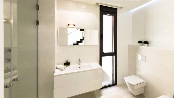 Baños de estilo  por arqubo arquitectos