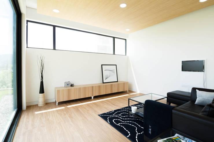 강이 보이는 언덕 위의 모던하우스, 양평 'Y' 주택: 스튜디오메조 건축사사무소의  거실
