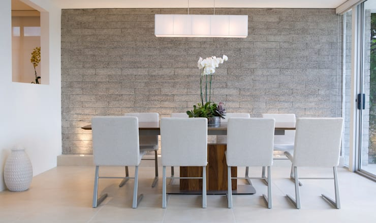 Grey Exposed Brick Dining Room:  Dining room by Gracious Luxury Interiors