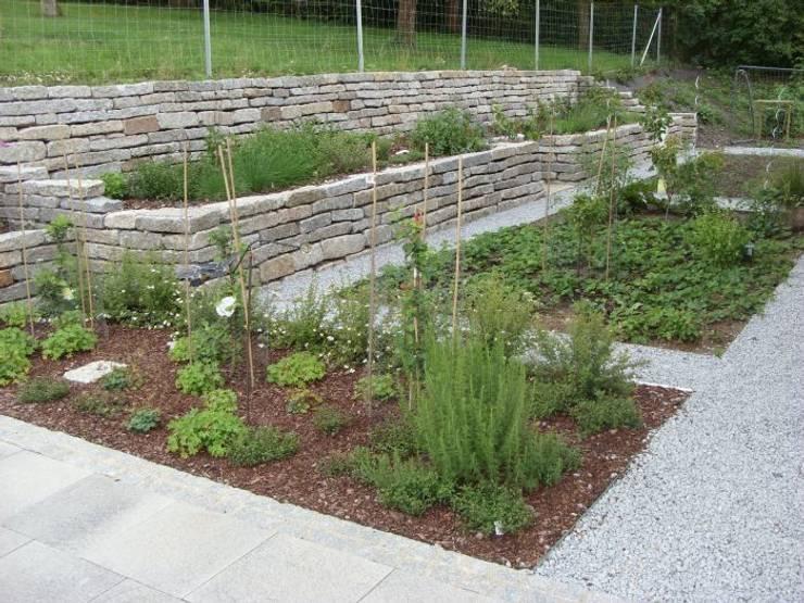 Der Höhenunterschied zum Nachbargarten wurde mit relativ rustikal wirkenden Trockenmauern aus gebrauchten, liegend verbauten Granit-Bordsteinen abgefangen.:  Garten von KAISER + KAISER - Visionen für Freiräume GbR