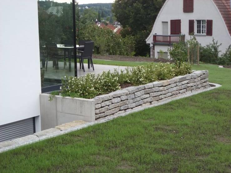 Kleines Pflanzbeet an der Terrasse: an der Schmalseite L-Steine aus Beton, längs wieder die gebrauchten Granit-Bordsteine.:  Garten von KAISER + KAISER - Visionen für Freiräume GbR