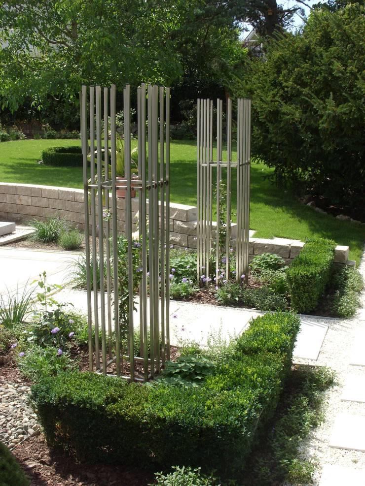 Extra angefertigte Rankgerüste für Clematis markieren den Zugang zur Terrasse.:  Garten von KAISER + KAISER - Visionen für Freiräume GbR