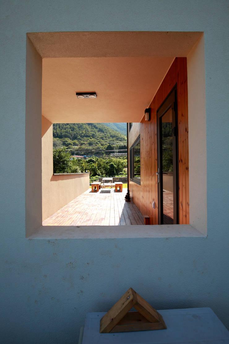울타리 안쪽의 집의 모습: 주택설계전문 디자인그룹 홈스타일토토의  베란다,모던