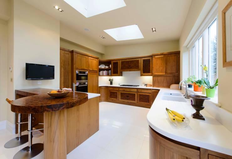 Walnut Curved Kitchen with White Corian Worktops: modern Kitchen by George Bond Interior Design