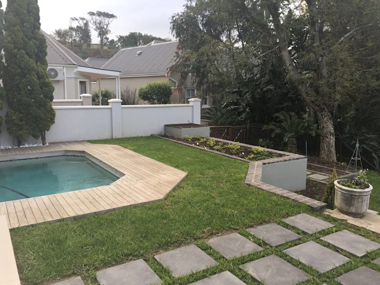 After picture of new lawn and paving near the pool.:  Garden by Helen Sparg Landscape Designer