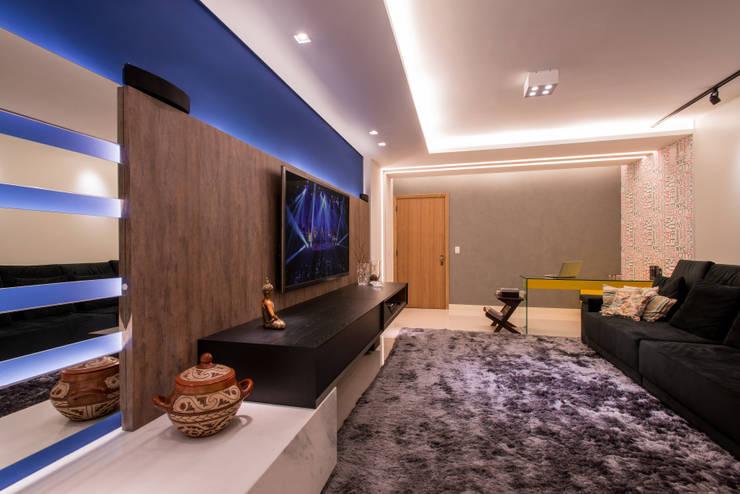 Sala de tv e lareira: Salas de estar  por C. Arquitetura