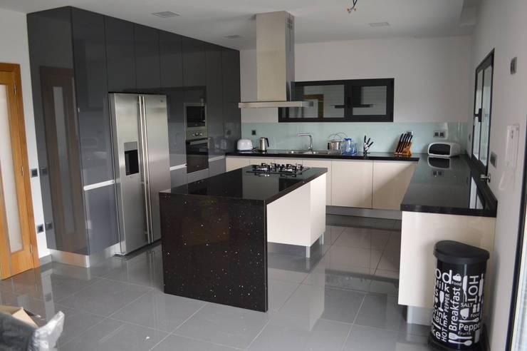Cozinha com ilha, colunas, forra de vidro e electrodomésticos encastrados: Cozinhas  por Ansidecor