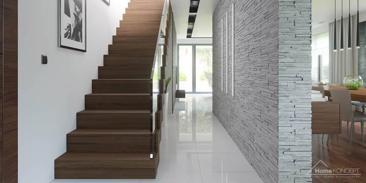 Pasillos y vestíbulos de estilo  por HomeKONCEPT | Projekty Domów Nowoczesnych