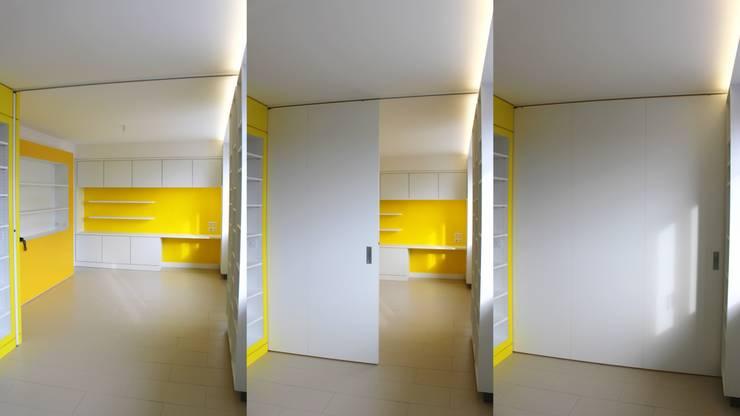 La séparation entre le séjour et la cuisine se fait par le biais d'une parois escamotable: Salon de style  par 3B Architecture