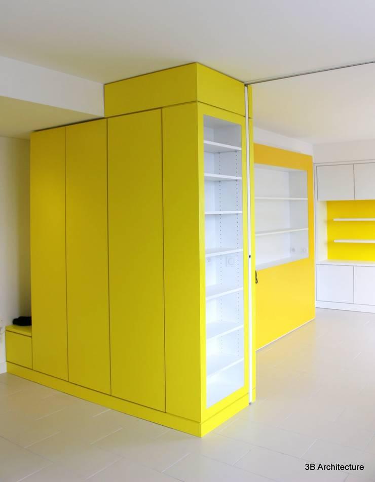 Le rythme et l'organisation des espaces se fait par le biais de meubles colorés qui qualifient subtilement les lieux tout en offrant des usages.: Couloir et hall d'entrée de style  par 3B Architecture